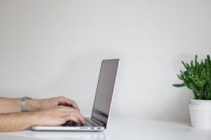 Pohľad zboku. Muž píše na počítači.