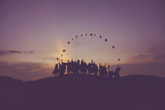 Študenti v talároch pri západe slnka.