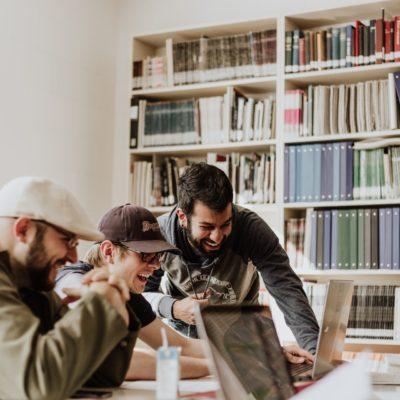 Trojica mužov v zdieľanom pracovnom prostredí sa smeje pri pohľade na počítačovú obrazovku.